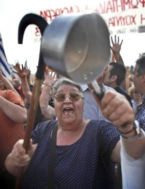 A demonstrator bangs on a pot during a peaceful rally outside the Greek Parliament in Athens, Sunday, June 5, 2011. Thousands of protesters gathered for a 12th consecutive day to protest at fiscal austerity measures and demand that Greece stop paying its debtors. They have also denounced politicians of all stripes as incompetent and corrupt. (AP Photo/Kostas Tsironis)