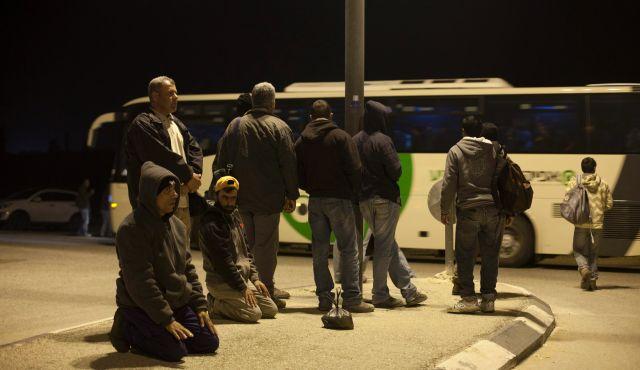 کارگران فلسطینی در انتظار اتوبوس برای رسیدن به محل کار در اسرائیل