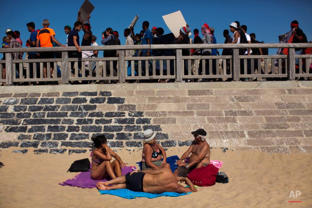شنبه هشتم اوت ۲۰۱۵: پناهجویان در حال گذر از کنار افرادی که در ساحل کاله آفتاب میگیرند در جریان تظاهراتی در اعتراض به وضعیتشان.