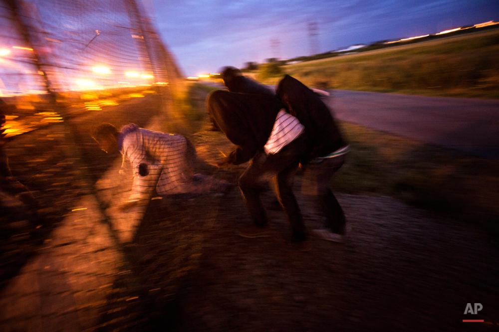 دوشنبه سوم اوت ۲۰۱۵: پناهجویان در حال عبور شبانه از توری فلزی منتهی به تونل اروپا.