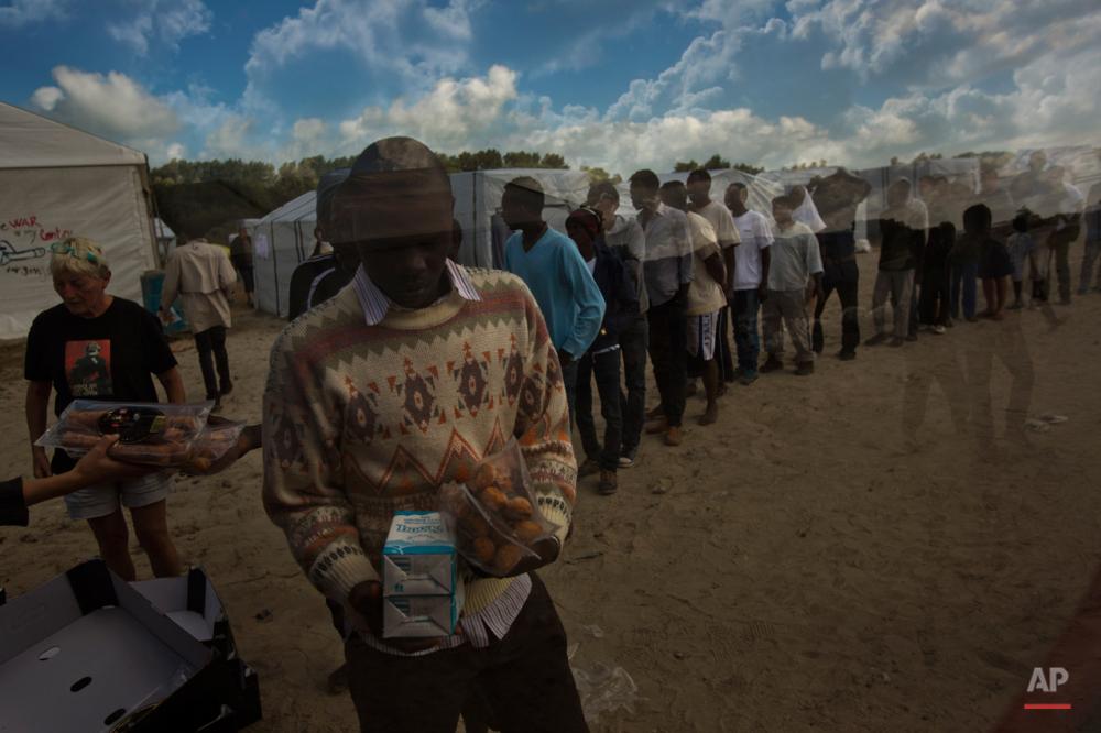 سهشنبه چهارم اوت ۲۰۱۵: پناهجویان در حال دریافت بستههای غذایی روزانهشان در بندر کاله فرانسه.