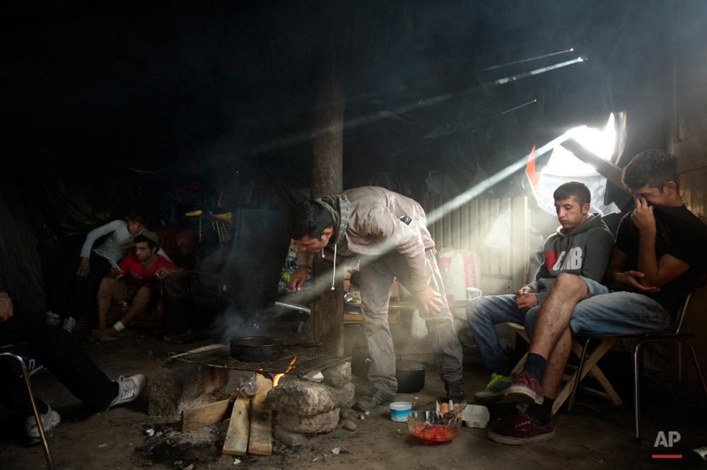 یکشنبه نهم اوت ۲۰۱۵: پناهجویان افغان در درون چادرشان در حال پخت غذا