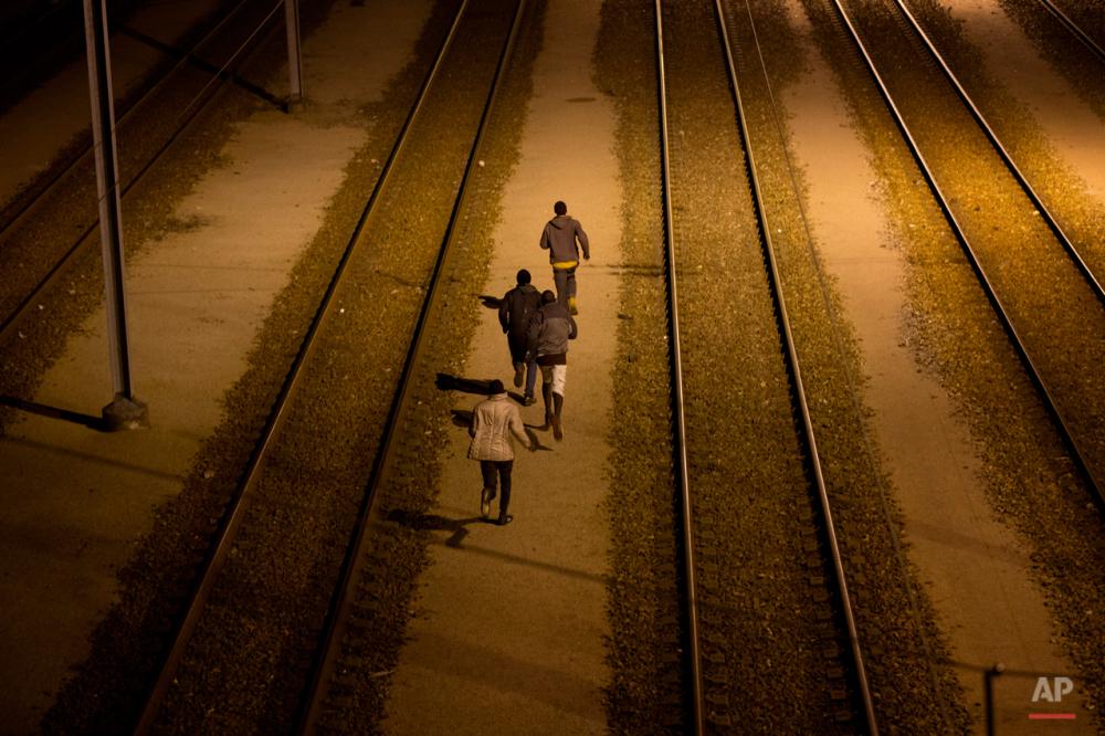 سهشنبه چهارم اوت ۲۰۱۵: پناهجویان در حال دویدن در کنار خطوط ریلی که به تونل اروپا منتهی میشود. در آن سوی تونل، انگلستان هدف نهایی پناهجویان قرار دارد.