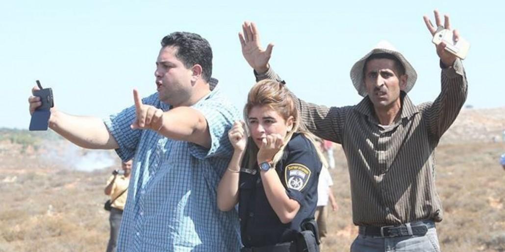 فلسطینیان از مامور پلیس اسرائیلی در مقابل شهرک نشینان یهودی افراطی محافظت میکنند.