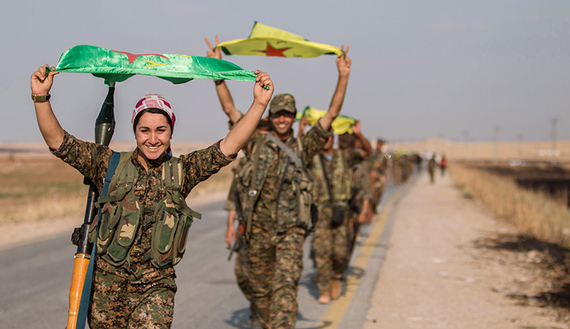 Kurdish fighters gesture while carrying their parties' flags in Tel Abyad of Raqqa governorate after they said they took control of the area June 15, 2015. Syrian Kurdish-led forces said they had captured a town at the Turkish border from Islamic State on Monday, driving it away from the frontier in an advance backed by U.S.-led air strikes that has thrust deep into the jihadists' Syria stronghold. The capture of Tel Abyad by the Kurdish YPG and smaller Syrian rebel groups means the Syrian Kurds effectively control some 400 km (250 miles) of the Syrian-Turkish border that has been a conduit for foreign fighters joining Islamic State. Picture taken June 15, 2015. REUTERS/Rodi Said TPX IMAGES OF THE DAY - RTX1GPFR