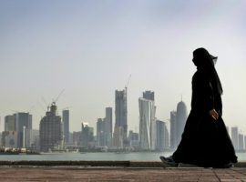 FILE- In this Friday, May 14, 2010 file photo, a Qatari woman walks in front of the city skyline in Doha. Qatar National Bank was responding to files circulating on social media that purport to show the personal information of hundreds of people, including staff at the broadcaster Al-Jazeera and members of the ruling family. (AP Photo/Kamran Jebreili)