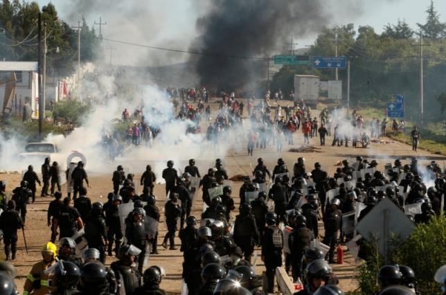 Protesters from the National Coordination of Education Workers (CNTE) teachers' union clash with riot police officers during a protest against President Enrique Pena Nieto's education reform, in the town of Nochixtlan, northwest of the state capital, Oaxaca City, Mexico June 19, 2016. REUTERS/Jorge Luis Plata